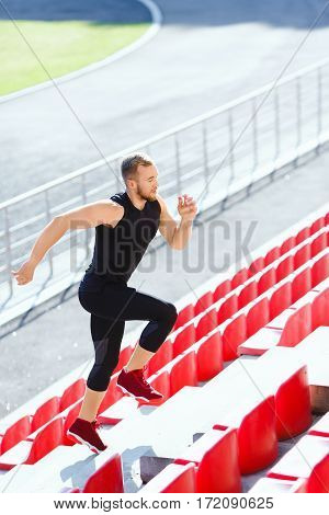 Full body of sportsman running up on tribune of stadium. Profile of man in black training suit and red sneakers. Outdoors, sunlight, stadium, doing sport