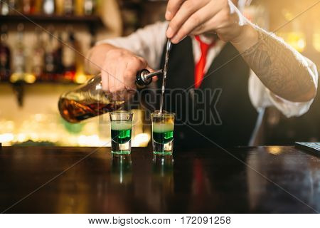 Barman making attractive alcoholic cocktail