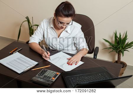 Female bookkeeper in glasses working at the table