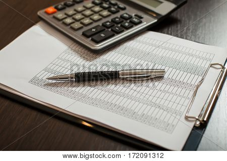 Accounting documents, pens and calculator closeup