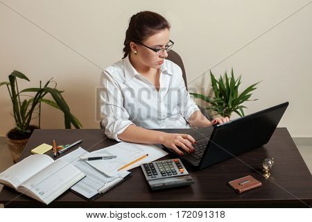 Female bookkeeper in glasses using laptop