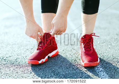 Sport concept, red sneakers for running. Man tightening lacings on his sneakers, no face. Legs in professional sport shoes. Outdoors, sunlight, stadium