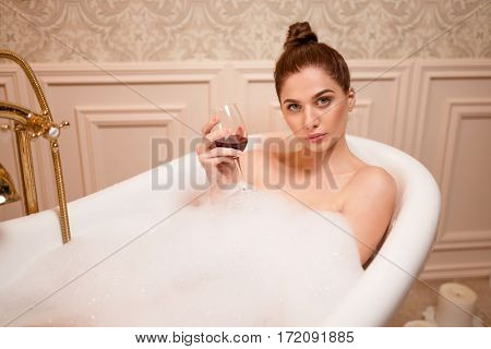Woman with glass of red wine in the bathtub
