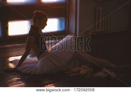 Ballerina sitting on floor in dark ballet class