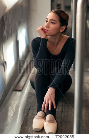 Female ballet dancer sitting against window