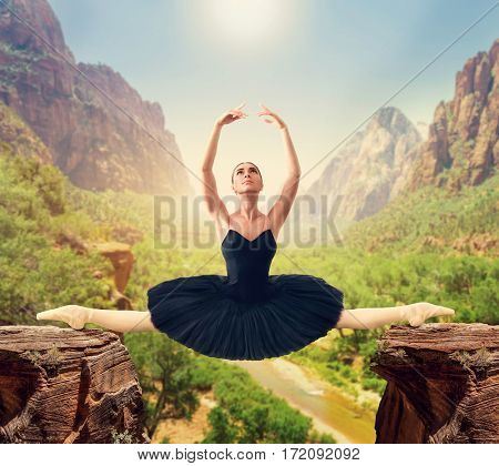 Graceful ballerina sit on the twine over the gorge