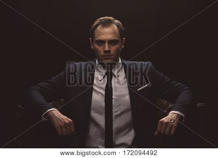 Portrait of a businessman in a suit on black background