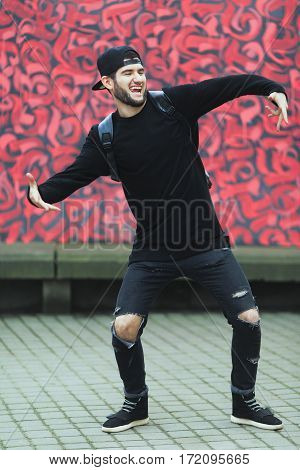 Man standing near colorful wall. Boy in torn jeans, black T-shirt and black cap with rucksack. Smiling, hands aside, dancing. Outside