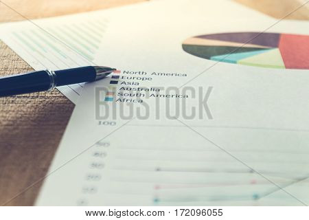 Close up pen with summary report and eyeglasses on table office. Concept of Data Analysis Investment Planning Business Analytics.