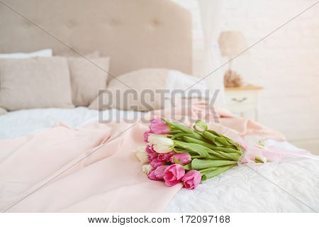 Nice bouquet with pink and white tulips lie on bed in the light room at the morning