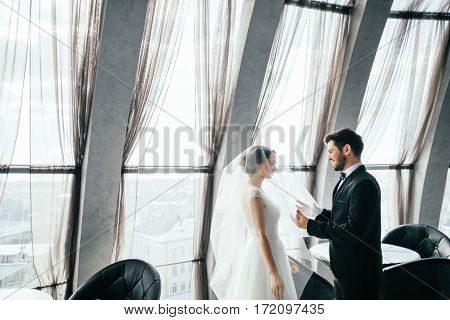 Gorgeous brunette bride and bridegroom standing close to each other at big window at background, wedding photo.