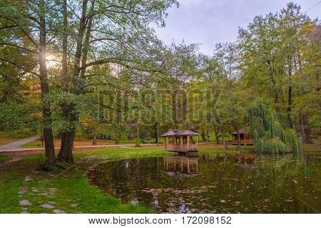 Autumn Park With Pond And Wooden Alcoves.