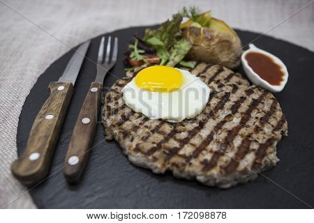 Big, juicy, delicious beefsteak with a fried egg and baked potatoes on a stone plate