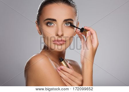 Stunning girl with brown hair fixed behind, clean fresh skin, big eyes and naked shoulders posing with mascara at gray studio background, make up model, cosmetics.
