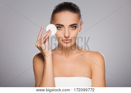 Pretty girl with brown hair fixed behind, clean fresh skin, big eyes and naked shoulders holding a cosmetic cleaning sponge, posing at gray studio background, a model with light nude make-up.