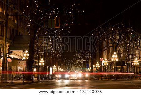 Vancouver Canada - January 28 2017: Gastown Vancouver at night with lights in the trees and light trails from the traffic.