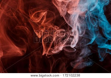 Abstract smoke Weipa. Personal vaporizers fragrant steam. The concept of alternative non-nicotine smoking. Orange blue smoke on a black background. E-cigarette. Evaporator. Taking Close-up. Vaping.