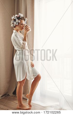 Young attractive housewife from the panoramic windows. Girl in a bathrobe and curlers drinking morning coffee. Good morning. She enjoys a hot drink