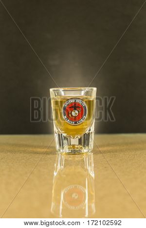 USMC shot glass, whiskey filled, reflected  in bar top