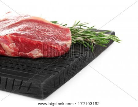 Cutting board with raw steak and spices on white background
