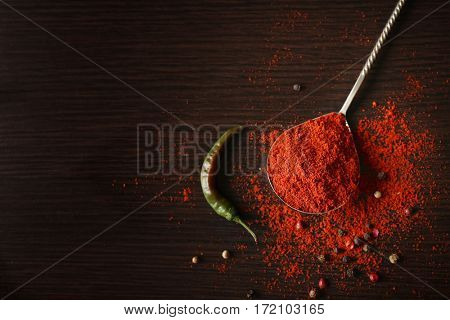 Spoon with paprika powder and chili pepper on wooden background