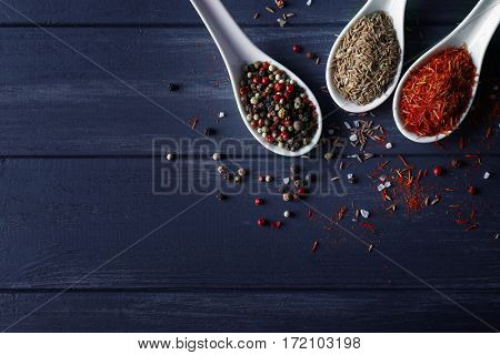 Assortment of spices in ceramic spoons on wooden background