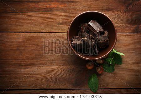 Broken chocolate pieces in bowl, close up