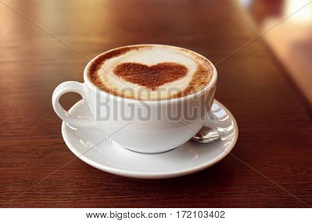 Cup with hot tasty coffee on wooden table, close up view