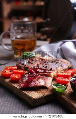 Grilled steak with tomatoes on cutting board and mug of beer on table