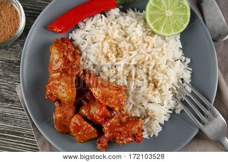 Portion of chicken tikka masala with rice on grey wooden table