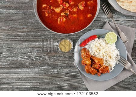 Chicken tikka masala in pan and portion with rice on grey wooden table