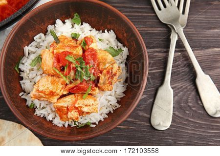 Portion of chicken tikka masala and rice in bowl on wooden table