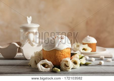 Glazed Easter cake and flowers on wooden table