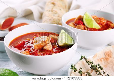 Portions of chicken tikka masala on white wooden table