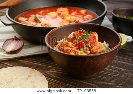 Chicken tikka masala with rice in bowl on wooden table