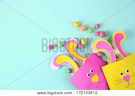 Easter decorative bunny bags with candies on color background