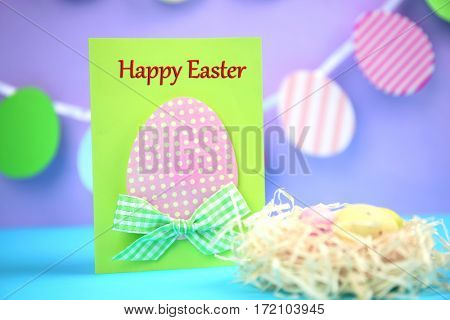 Easter concept. Greeting card and decorative nest with eggs on blue table