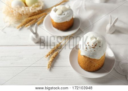 Plates with sweet Easter cakes on table