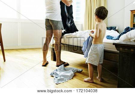 A boy is trying to put on a outfit.