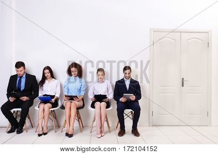 Group of people waiting for job interview in a hall
