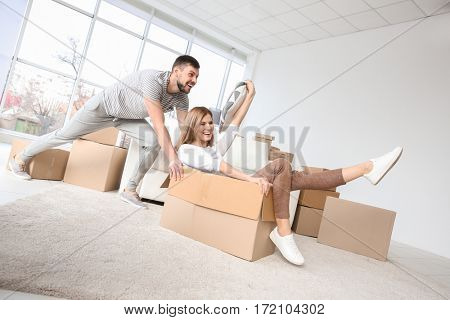 Young happy couple packing and having fun. Moving concept