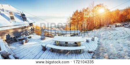Cabin in the mountains in winter. Mysterious fog. Fantastic sunlight in the morning. Fantastic days of November. Carpathian. Ukraine, Europe