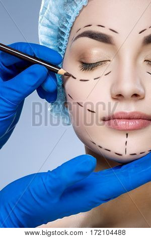 Nice girl with dark eyebrows wearing blue medical hat at studio background, doctor's hand making perforation lines on patient's face, portrait.