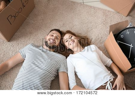 Happy family couple lying with cardboard boxes at home