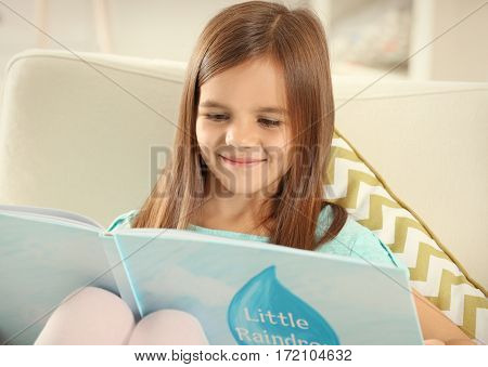 Cute little girl with book sitting on armchair at home