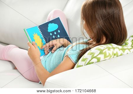 Attractive little girl with book sitting on sofa at home