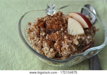 Healthy breakfast - oat flakes with grated apple and mashed banana sprinkled with cinnamon