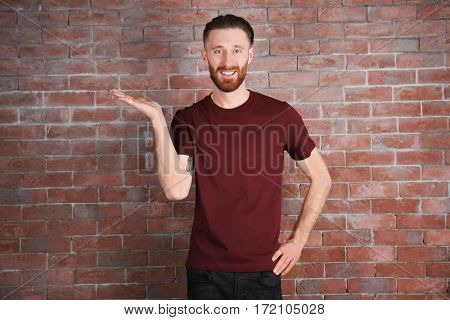 Young handsome man in claret red T-shirt on brick wall background