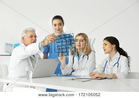 Team of doctors exploring roentgenogram at table