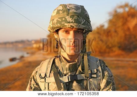 Portrait of soldier in camouflage at sunset